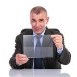 De bedrijfsmens houdt een transparant paneel Stock Afbeelding
