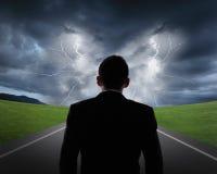 De bedrijfsmens kijkt stortbuiwolken en bliksem Royalty-vrije Stock Afbeelding