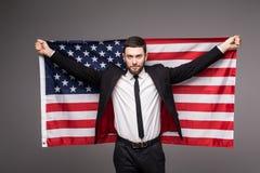 De bedrijfsmens in kostuumholding de V.S. markeert van zijn rug met open mond Royalty-vrije Stock Foto's