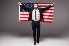 De bedrijfsmens in kostuumholding de V.S. markeert van zijn rug met open mond Royalty-vrije Stock Foto