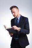 De bedrijfsmens leest een boek Stock Afbeeldingen