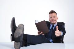 De bedrijfsmens leest met voeten op bureau Royalty-vrije Stock Fotografie