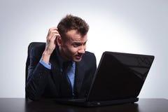 De bedrijfsmens leest op zijn laptop Royalty-vrije Stock Afbeelding