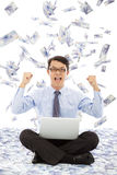 De bedrijfsmens maakt een overwinningsgebaar met geldregen Royalty-vrije Stock Afbeelding