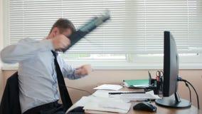 De bedrijfsmens, manager in woede breekt toetsenbord op bureau, zittend in bureau stock footage