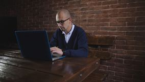 De bedrijfsmens met glazen typt tekst op laptop toetsenbord Het werk van een freelancer stock video