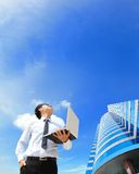 De bedrijfsmens met laptop en kijkt hemel en wolk Royalty-vrije Stock Afbeelding