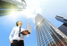De bedrijfsmens met laptop en kijkt hemel en wolk Royalty-vrije Stock Foto