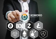 De bedrijfsmens richt zijn vinger onder andere op Komodo-muntstukpictogram Cryptocurrency op Virtueel Touch screen royalty-vrije stock foto's