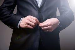 De bedrijfsmens ruimt de knoop van zijn kostuum op, maakt een keurig beeld Stock Fotografie