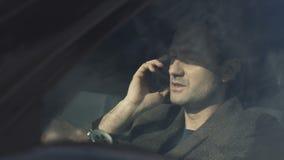 De bedrijfsmens spreekt door telefoonzitting in auto stock videobeelden