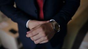 De bedrijfsmens start zijn mechanisch horloge op stock videobeelden