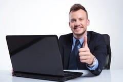 De bedrijfsmens toont duim achter laptop Stock Fotografie