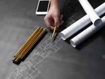 De bedrijfsmens trekt gebouwen en stelt zijn architecturale projec voor Stock Foto's