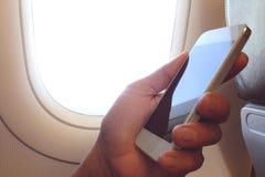 De bedrijfsmens zit in vliegtuig lettend op zijn celtelefoon Royalty-vrije Stock Afbeeldingen