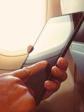 De bedrijfsmens zit in vliegtuig lettend op zijn celtelefoon Royalty-vrije Stock Afbeelding