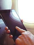 De bedrijfsmens zit in vliegtuig lettend op zijn celtelefoon Stock Foto's