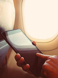 De bedrijfsmens zit in vliegtuig lettend op zijn celtelefoon Royalty-vrije Stock Fotografie