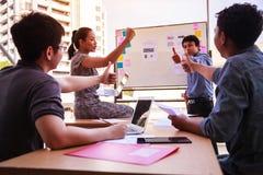 De bedrijfsmensen beduimelen omhoog over lijst in een plannende vergadering op modern kantoor Groepswerk, diversiteit, samenwerki stock afbeelding