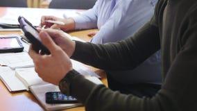 De bedrijfsmensen bij bestuurskamer dienen het bespreken van financieel verslag in gebruikend gegevens en gadget stock videobeelden