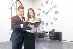 De bedrijfsmensen in bureau met grote muur klokken Stock Afbeelding