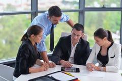 De bedrijfsmensen groeperen zich in een vergadering op kantoor stock afbeelding