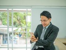 De bedrijfsmensenzitting op zijn schijf en controleert zijn mobiele telefoon stock afbeeldingen