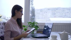 De bedrijfsontwikkeling, jonge vrouw in oogglazen die laptop met behulp van en schrijft nota's met blauwe teller in notitieboekje stock video
