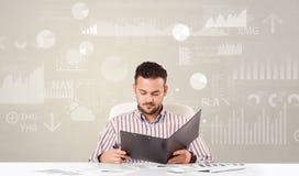 De bedrijfspersoonszitting bij bureau met rapport analyseert concept stock foto