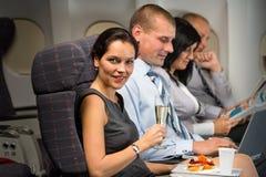 De bedrijfsreis door vliegtuigvrouw geniet van verfrissing Stock Afbeelding