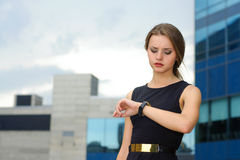 De bedrijfsvrouw bekijkt zorgvuldig haar polshorloge royalty-vrije stock afbeelding