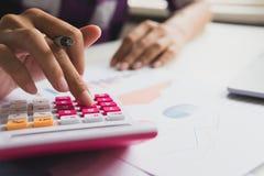 De bedrijfsvrouw berekent over kosten en het doen van financiën op kantoor royalty-vrije stock afbeeldingen