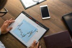 De bedrijfsvrouw bij werkplaats bij houten bureaulijst analyseert de gegevens, programma's, prijzen, maakt berekeningen op een ca Royalty-vrije Stock Foto's