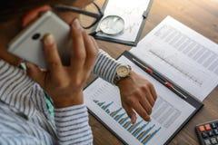 De bedrijfsvrouw bij werkplaats bij houten bureaulijst analyseert de gegevens, programma's, prijzen, maakt berekeningen op een ca Royalty-vrije Stock Fotografie
