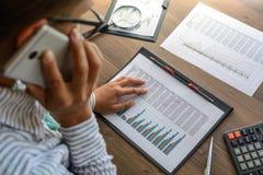 De bedrijfsvrouw bij werkplaats bij houten bureaulijst analyseert de gegevens, programma's, prijzen, maakt berekeningen op een ca Stock Foto