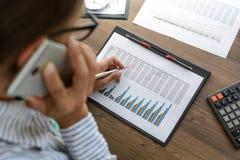 De bedrijfsvrouw bij werkplaats bij houten bureaulijst analyseert de gegevens, programma's, prijzen, maakt berekeningen op een ca Stock Fotografie