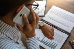 De bedrijfsvrouw bij werkplaats bij houten bureaulijst analyseert de gegevens, programma's, prijzen, maakt berekeningen op een ca Royalty-vrije Stock Afbeelding
