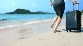 De bedrijfsvrouw in bureaukleren loopt blootvoets aan het overzees langs een wit zandig strand freelance, langverwachte vakantie royalty-vrije stock afbeeldingen