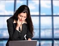 De bedrijfsvrouw denkt probleem aangaande computer na Stock Foto