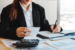 De bedrijfsvrouw die Financiële investering op calculator rekenschap geven kostte Economische zaken en markt royalty-vrije stock foto