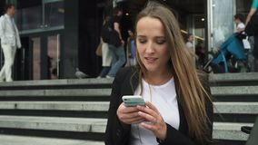 De bedrijfsvrouw die smartphone gebruiken dichtbij ingang aan de stadsbouw, mensen gaat erachter stock footage