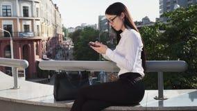 De bedrijfsvrouw die smartphone gebruiken terwijl het werken aan gaat bij stedelijke straat stock video