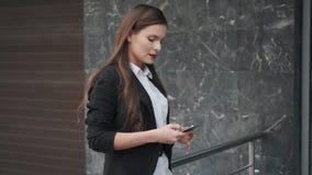 De bedrijfsvrouw in een jasje verzendt een bericht van smartphone portret van een jonge vrouw met een mobiele telefoon in haar stock video