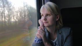 De bedrijfsvrouw gaat door trein, bekijkend uit het venster het de lentelandschap stock video