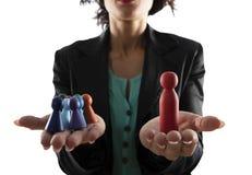 De bedrijfsvrouw houdt houten stuk speelgoed dat als persoon wordt gevormd Concept bedrijfsgroepswerk en leiding Ge?soleerd op wi stock fotografie