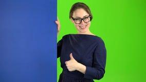 De bedrijfsvrouw kijkt uit van achter een blauwe raad en toont duimen Het groene scherm stock videobeelden