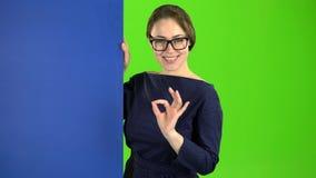 De bedrijfsvrouw kijkt uit van achter een blauwe raad en toont o.k. Het groene scherm stock video