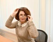 De bedrijfsvrouw met een glimlach kijkt over glazen, houdend de tweede glazen op het hoofd Royalty-vrije Stock Fotografie