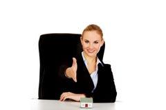 De bedrijfsvrouw met een open hand klaar voor handdruk en het huis modelleren op het bureau royalty-vrije stock foto's