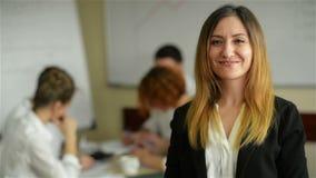 De bedrijfsvrouw met haar personeel, mensen groepeert zich binnen op achtergrond op modern helder kantoor stock video